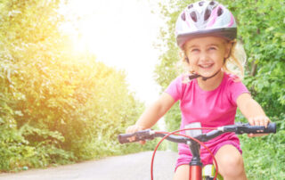 Happy Child Riding A Bike In Outdoor with airpop helmet